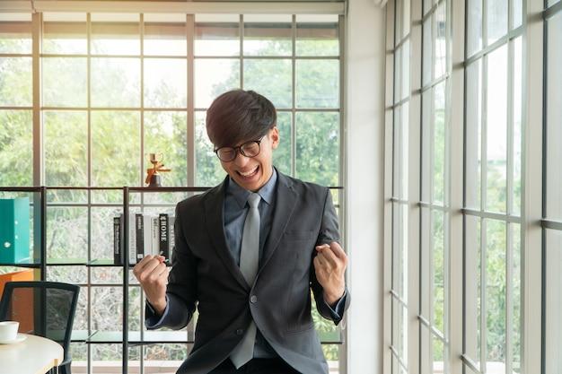 De jonge aziatische zakenman wekte gelukkig en het vieren succes op de werkplaats op.
