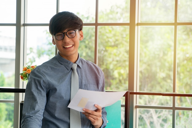 De jonge aziatische zakenman wekte gelukkig en het vieren succes op de werkplaats op