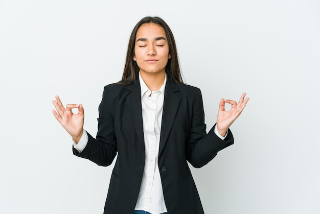 De jonge aziatische zakenvrouw die op witte muur wordt geïsoleerd, ontspant na een harde werkdag, zij voert yoga uit.