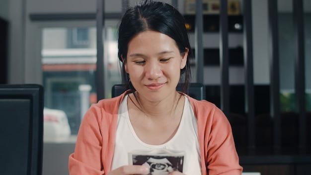 De jonge aziatische zwangere vrouwen tonen en kijkend de baby van de ultrasone klankfoto in buik. mamma die het gelukkige vreedzame glimlachen voelen terwijl thuis de zitting van het zorgkind op lijst in woonkamer thuis nemen.