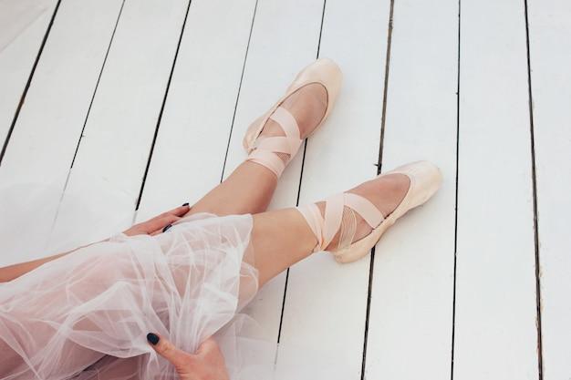 De jonge balletdanser van de vrouwen authentieke ballerina in pointe shous zitting op witte vloer