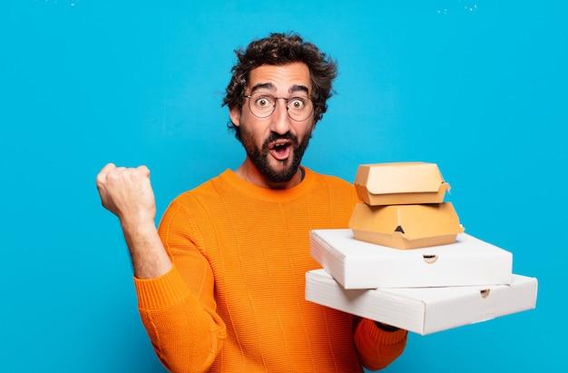 De jonge, bebaarde man haalt fastfoodconcept weg
