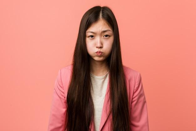 De jonge bedrijf chinese vrouw die roze kostuum draagt blaast wangen, heeft vermoeide uitdrukking.