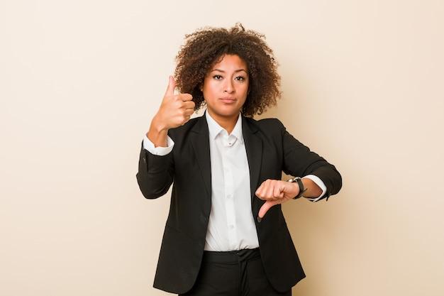De jonge bedrijfs afrikaanse amerikaanse vrouw die duimen tonen en duimen neer, kiest moeilijk