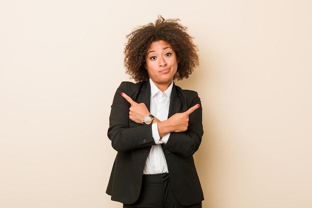 De jonge bedrijfs afrikaanse amerikaanse vrouw richt zijdelings, probeert tussen twee opties te kiezen.
