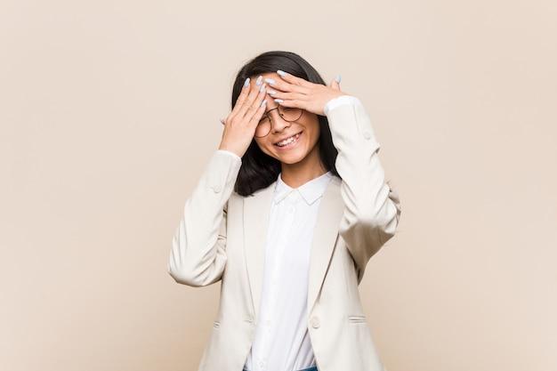 De jonge bedrijfs chinese vrouw behandelt ogen met handen, glimlacht globaal wachtend op een verrassing.
