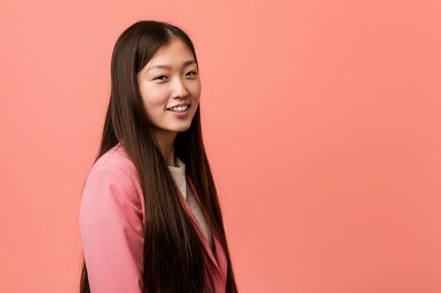 De jonge bedrijfs chinese vrouw die roze kostuum draagt kijkt opzij glimlachend, vrolijk en aangenaam.