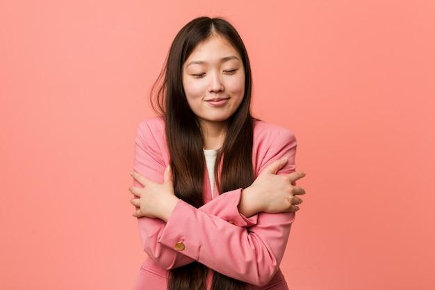 De jonge bedrijfs chinese vrouw die roze kostuum draagt koestert zich, onbezorgd en gelukkig glimlachen.