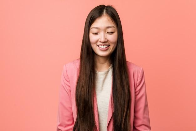 De jonge bedrijfs chinese vrouw die roze kostuum draagt lacht en sluit ogen, voelt ontspannen en gelukkig.