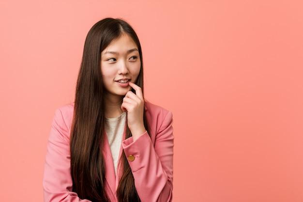 De jonge bedrijfs chinese vrouw die roze kostuum draagt ontspande het denken over iets bekijkend een exemplaarruimte.