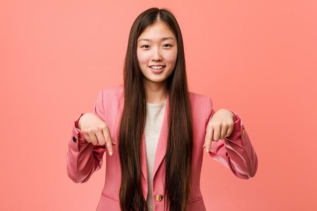 De jonge bedrijfs chinese vrouw die roze kostuum draagt wijst neer met vingers, positief gevoel.