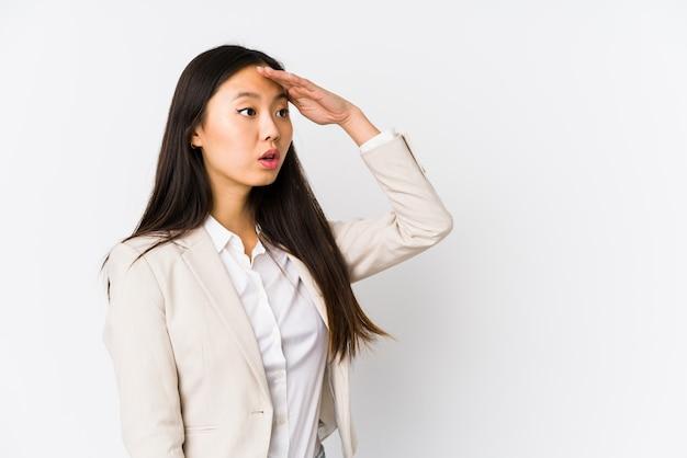 De jonge bedrijfs chinese vrouw isoleerde het kijken ver weg houdend hand op voorhoofd.