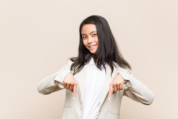 De jonge bedrijfs chinese vrouw wijst neer met vingers, positief gevoel.