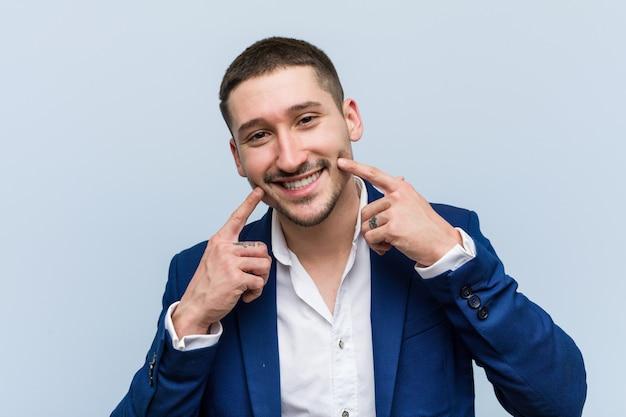 De jonge bedrijfs kaukasische mens glimlacht, die vingers richten op mond.