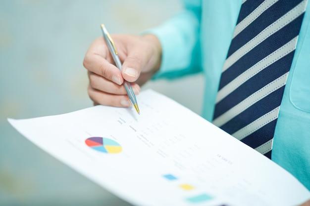 De jonge bedrijfs slimme manager die met nieuw succes startproject werken analyseert grafiekplan.