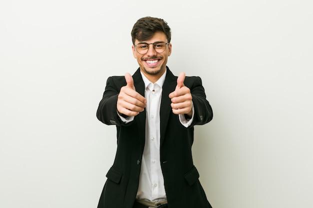 De jonge bedrijfs spaanse mens met duimen ups, juicht over iets, steun en eerbiedconcept toe.