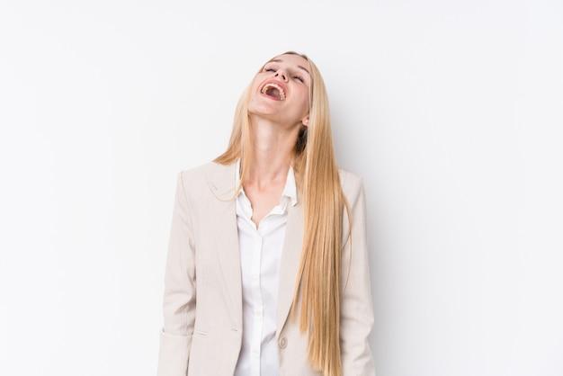 De jonge bedrijfsblondevrouw op witte muur ontspande en het gelukkige lachen, uitgerekte hals tonend tanden.
