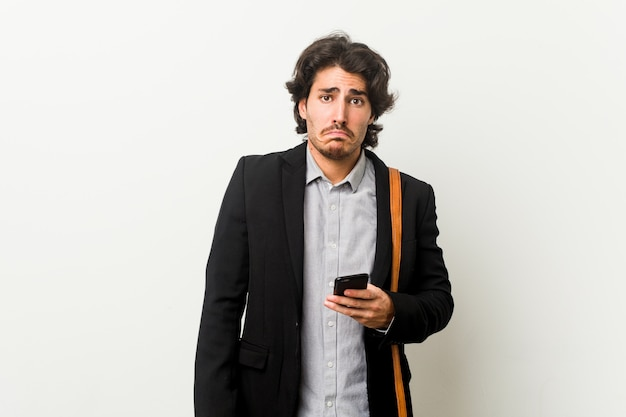 De jonge bedrijfsmens die een telefoon houdt haalt schouders en open ogen op verward.