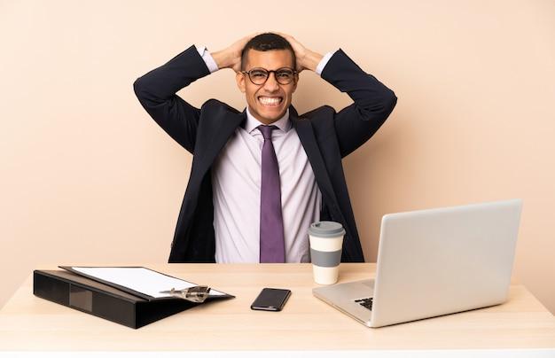 De jonge bedrijfsmens in zijn bureau met laptop en andere gefrustreerde documenten en neemt handen op hoofd