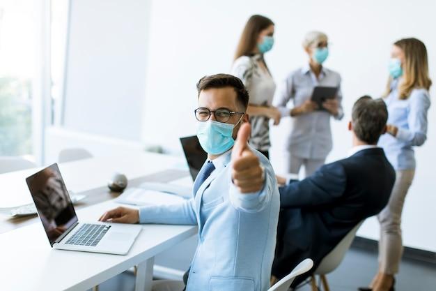 De jonge bedrijfsmens met medisch beschermend masker werkt aan laptop in het bureau en toont positief duimgebaar