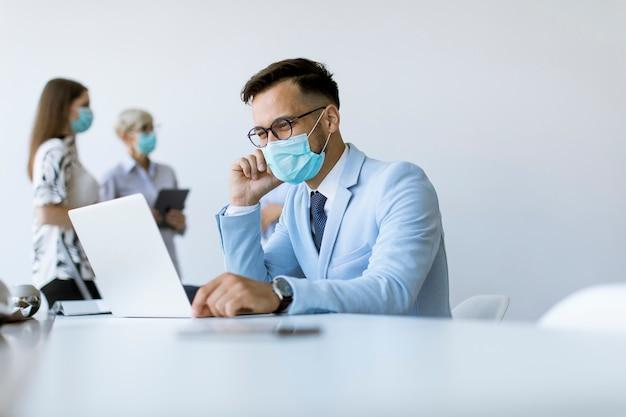 De jonge bedrijfsmens met medisch beschermend masker werkt aan laptop