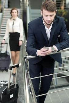 De jonge bedrijfsmensen in luchthaven wachten vliegtuigen.