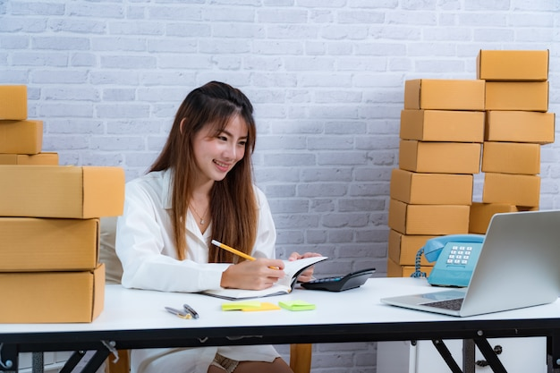 De jonge bedrijfsondernemerseigenaar schrijft in de levering in notitieboekje over online leveringszaken