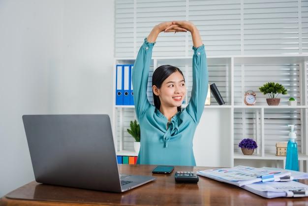 De jonge bedrijfsvrouw die thuis werkt heft haar handen op om van hard werken, coronavirus te ontspannen.