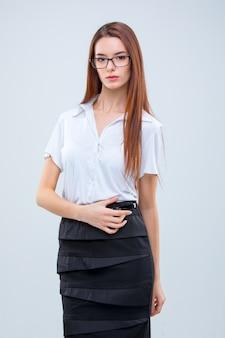De jonge bedrijfsvrouw in glazen op grijs