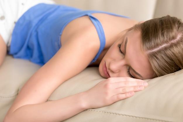 De jonge berooide slaapvrouw die in slaap op bank liggen, sluit omhoog