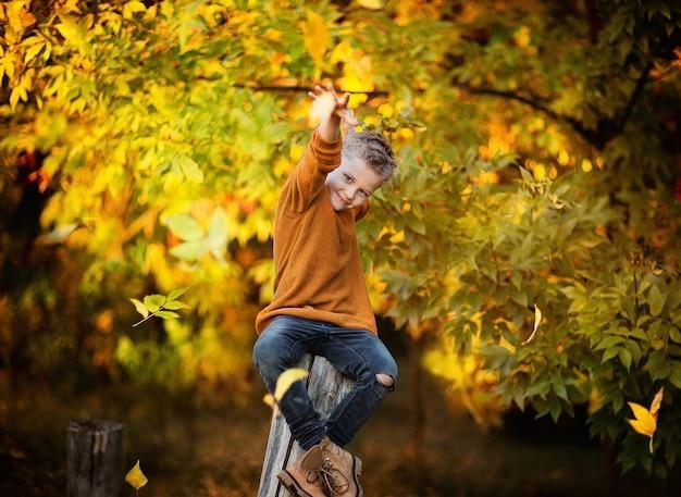 De jonge bladeren die van de jongens trowing herfst op een houten stomp in een park zitten. herfst achtergrond. kopieer ruimte.