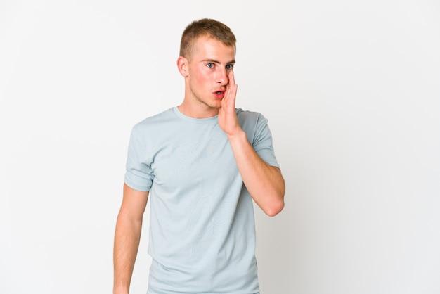 De jonge blanke knappe man zegt een geheim heet remmend nieuws en kijkt opzij