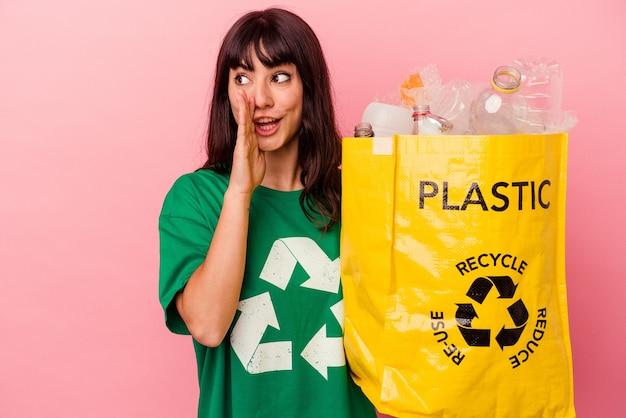 De jonge blanke vrouw die een gerecycleerde plastic zak houdt die op roze muur wordt geïsoleerd, zegt een geheim heet remmend nieuws en kijkt opzij