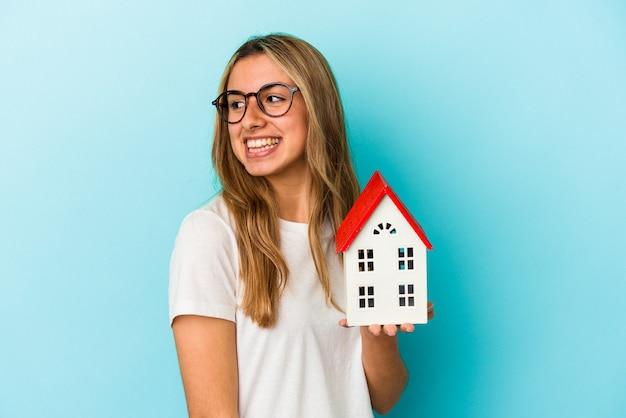 De jonge blanke vrouw die een huismodel houdt dat op blauwe achtergrond wordt geïsoleerd, kijkt opzij glimlachend, vrolijk en aangenaam.
