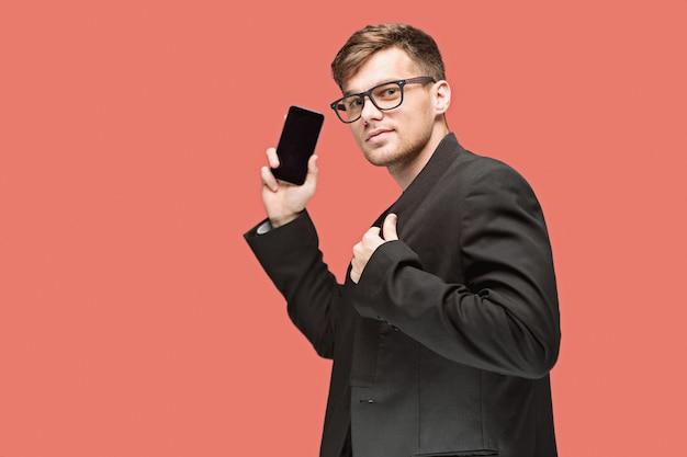 De jonge blanke zakenman op rode muur praten op mobiele telefoon
