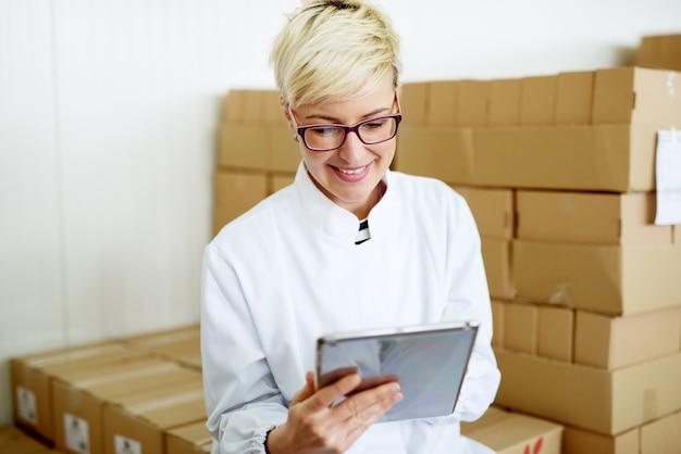 De jonge blije vrouwelijke technicus glimlacht terwijl het gebruiken van een tablet en leunend tegen de grote stapel kartondozen.