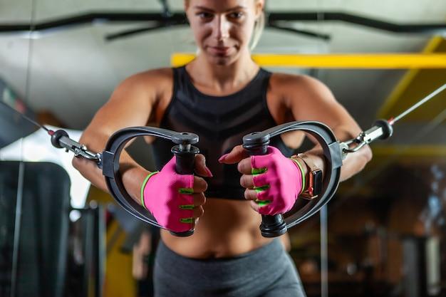De jonge blonde geschikte vrouw voert oefening met oefeningsmachine uit kabelovergang in gymnastiek. focus op handen