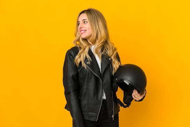 De jonge blonde kaukasische de holdingshelm van de fietservrouw kijkt opzij glimlachend, vrolijk en aangenaam.