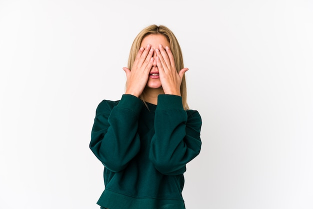 De jonge blonde kaukasische vrouw isoleerde bang behandelend ogen met handen.