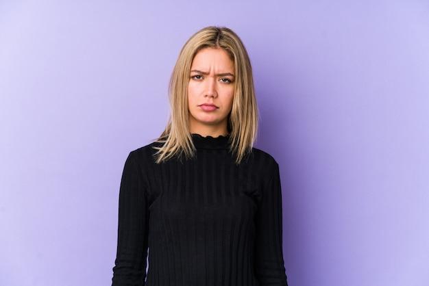 De jonge blonde kaukasische vrouw isoleerde droevig, ernstig gezicht, voelend ellendig en ontevreden.