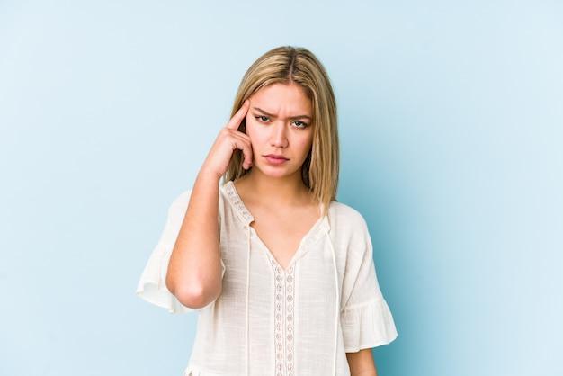 De jonge blonde kaukasische vrouw isoleerde het tonen van een teleurstellingsgebaar met wijsvinger.