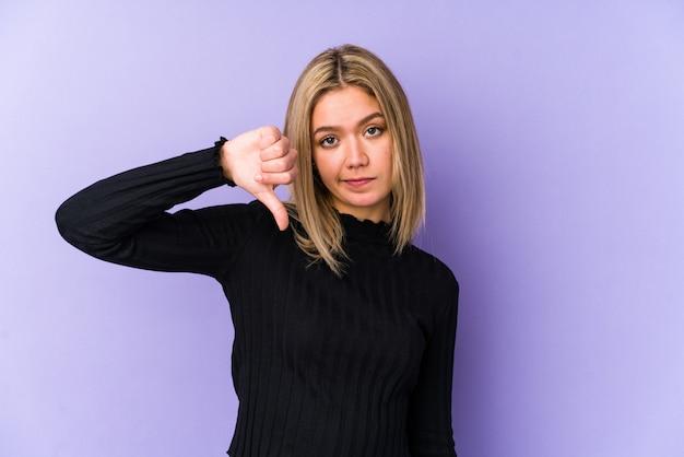 De jonge blonde kaukasische vrouw isoleerde neer tonend een afkeergebaar, duimen. meningsverschil concept.