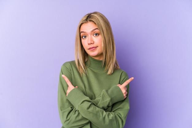 De jonge blonde kaukasische vrouw isoleerde zijdelings punten, probeert tussen twee opties te kiezen.