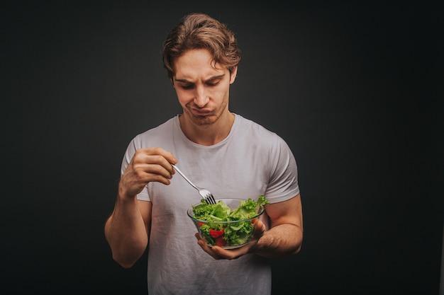 De jonge blonde mens in wit t-shirt houdt plaat van salade met teleur