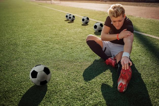 De jonge blonde voetbalster zit op gazon en rekt zich uit. hij reikt met één hand tot voeten. een andere is op de schouder. vier ballen achter hem en een bal vooraan.