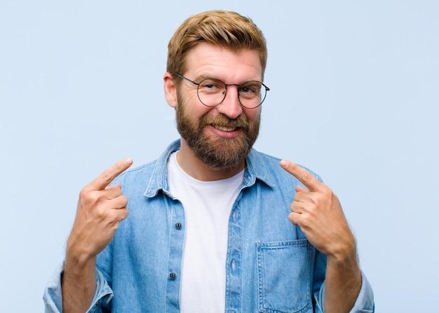 De jonge blonde volwassen mens die vol vertrouwen glimlachen wijzen op eigen brede glimlach positieve ontspannen tevreden houding