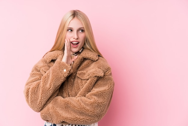 De jonge blonde vrouw die een roze jas draagt, zegt een geheim heet remmend nieuws en kijkt opzij
