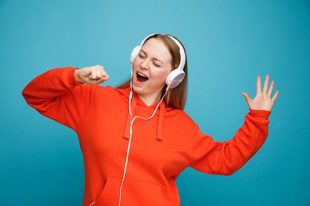 De jonge blonde vrouw die hoofdtelefoons draagt die hand opheft doen alsof ze microfoon zingen met gesloten ogen vasthouden