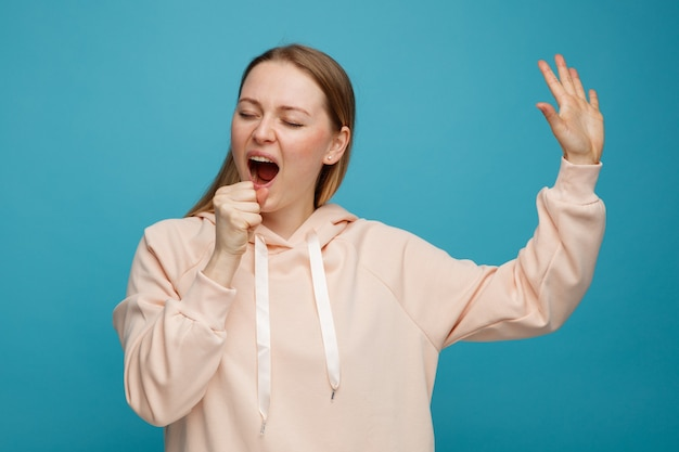 De jonge blonde vrouw doet alsof holdingsmicrofoon opheft die hand het zingen met gesloten ogen opheft
