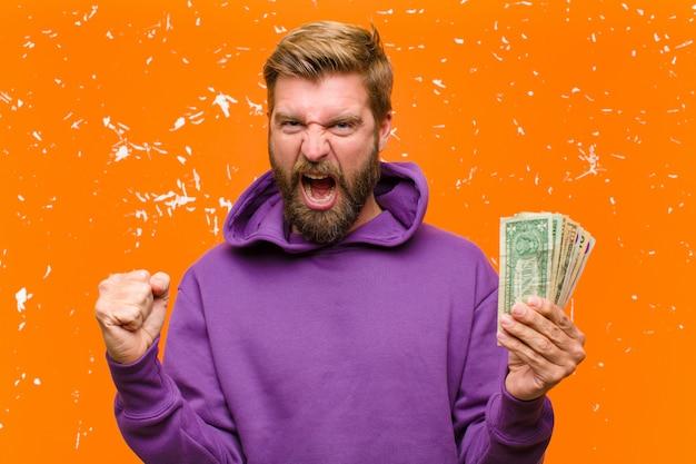 De jonge blondemens met dollarrekeningen of bankbiljetten die een purpere hoodie dragen beschadigde oranje muur